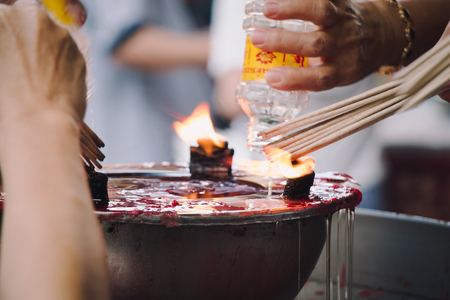 believable: Burning Joss stick and oil palm candle at chinese shrine for making merit in chinese new year festival. Pray for New Year, Lighting incense to Buddha.