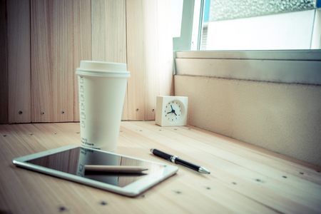 shutdown: Select focus Clock on table with  coffee cup and shutdown tablet, that near pen on the wood table background, relax time