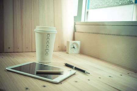 shutdown: Coffee cup with  shutdown tablet that near pen on the wood table background, relax time