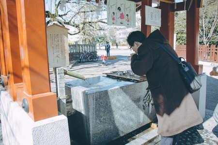 purification: Man, worshipper cleanse  body and spirit at water basin. chozuya or temizuya is the pavilion for purification where worshipper cleanse  body and spirit.