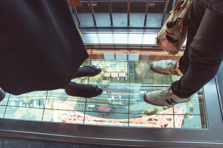 look down: feet of traveller stand in Mirror of Look down Window. High view from Tokyo tower.