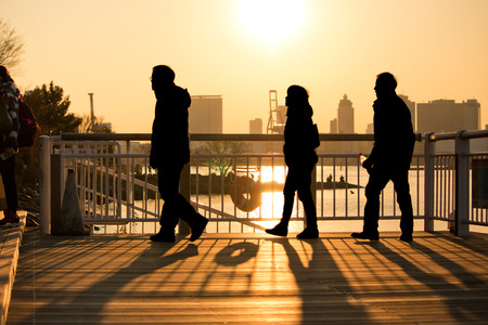human relations: Silhouette of traveller stand on terrace in the beach at sunset, Odaiba park, Tokyo Japan. Stock Photo