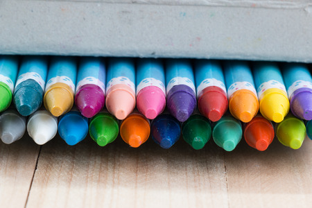 artboard: Close up set of crayon in the box on wood table background