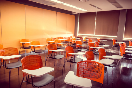 arm chairs: Empty classroom with orange arm chairs