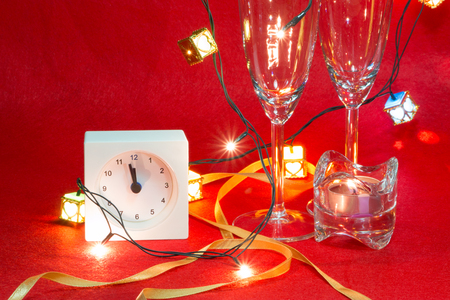 White Clock go forward overnight. Cool Champagne and couple glass celebrate in party. ornament by candlestick, ribbon, and light bulb.