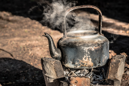 old aluminium kettle on stove.people is boiling water at the countryside in the sunset morning Stock Photo