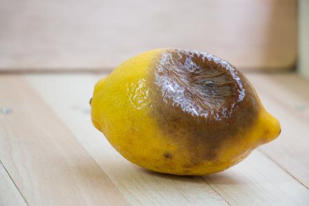 rotten lemon put on wooden table, isolate background Stock Photo