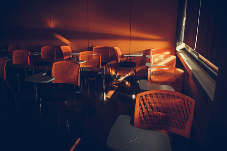 arm chairs: light pass under curtain in Finish class and end of semester, Empty classroom with orange arm chairs