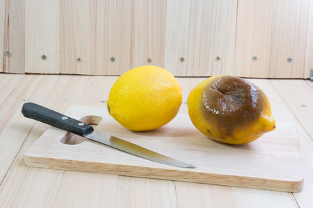 Fresh lemon and rotten lemon put on chopping block and knife, wooden table isolate background.