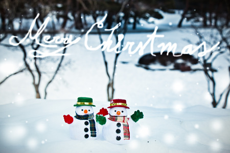 Snowman and friend stand among pile of snow in park. Morning sunshine is warming in winter. Welcome christmas season.