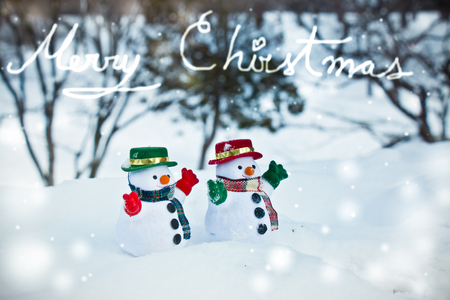 diamond candle: Snowman and friend stand among pile of snow in park. Morning sunshine is warming in winter. Welcome christmas season.