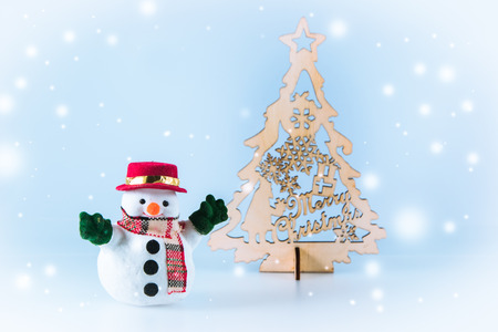 christmas frog: Snowman near christmas tree on white background. Snow flake is falling down.