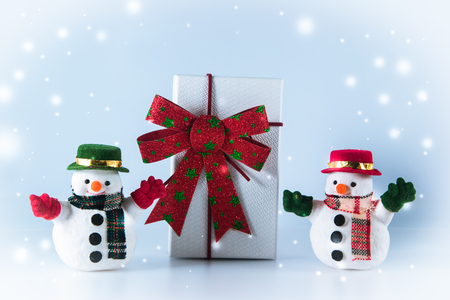 greet card: Snowman stand near gift box on white background. Snow flake is falling down.