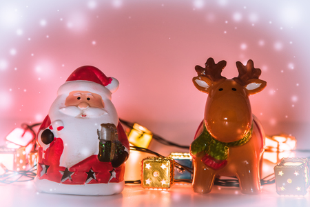 christmas frog: Santa claus and reindeer with light bulb stand on white background. Snow flake is falling down.