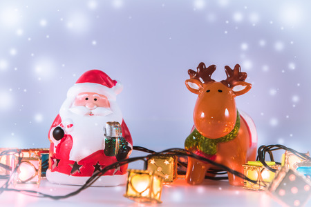 greet card: Santa claus and reindeer with light bulb stand on white background. Snow flake is falling down.