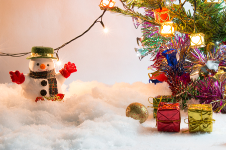 hopefulness: Snowman stand in pile of snow with a ornament and gift at silent night with a light bulb, light up the hopefulness and happiness in Merry christmas and happy new year night.