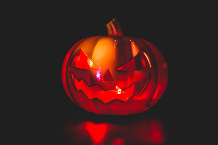 Halloween pumpkin party, Big terrible Pumpkin lighten and reflection on black background. Stock Photo
