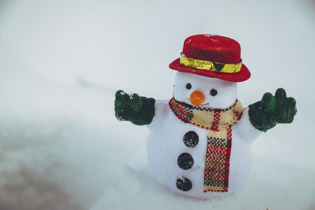 Snow man stand among pile of snow. Morning sunshine is warming in winter. Stock Photo