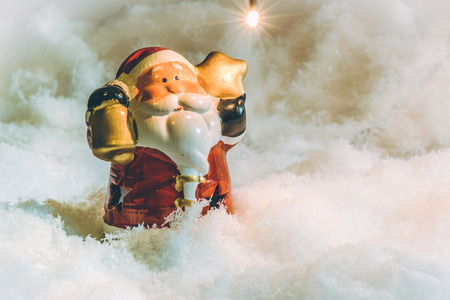 hopefulness: Santa claus hold the bell and star stand in pile of snow at silent night,  light up the hopefulness and happiness in Merry christmas and happy new year night.