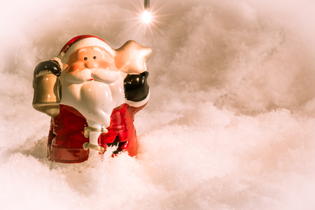 christmas frog: Santa claus hold the bell and star stand in pile of snow at silent night,  light up the hopefulness and happiness in Merry christmas and happy new year night.
