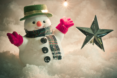 silent night: Snowman and light bulb stand in pile of snow at silent night, light up the hopefulness and happiness in Merry christmas and happy new year night. Stock Photo