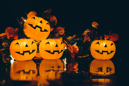 Halloween pumpkin party lighten,4 friends happy pumpkins lighten and reflection on black background.