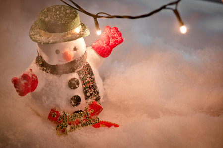 hopefulness: Snowman stand in pile of snow at silent night with a light bulb, light up the hopefulness and happiness in Merry christmas and happy new year night.