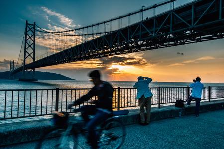 Bottom view of Akashi Kaikyo Bridge. The photography man take  a picture of Akashi Kaikyo Bridge with Sunset, the great architecture of spanning ,suspension bridge, Kobe, Japan
