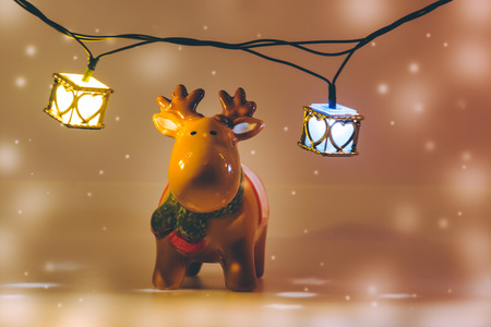 greet card: reindeer and light bulb stand on white background. Snow flake is falling down. Stock Photo