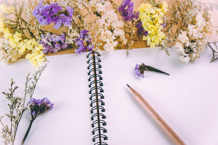 Flower blossom put on blank notebook, on wooden table