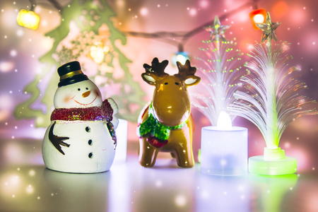 greet card: Reindeer and Snowman stand near christmas tree stand on white background. Snow flake is falling down. Stock Photo