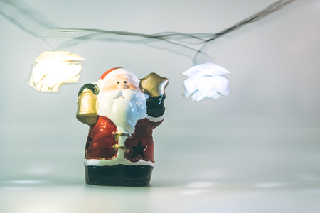christmas frog: Santa claus and light bulb stand on white background. Snow flake is falling down.