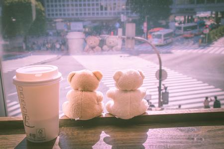union familiar: Los pares preciosos llevan y la taza de café se sientan juntos en la barra de madera cerca de la ventana, mire el cruce de Shibuya. Sol de la mañana en Tokio, Japón.