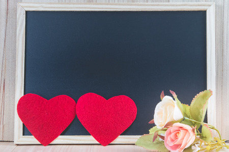 The 2 heart put on wooden floor with the blackboard and sweet roses., Valentine day concept