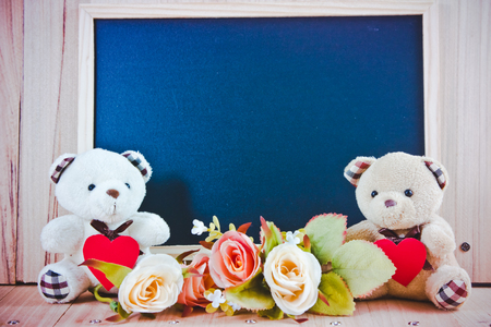 Lovely couple bear hold heart sit near sweet roses on the wooden floor with the black board, Valentine day concept Stock Photo
