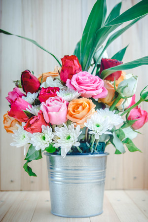 Vase of bouquet Roses in aluminium bucket on wooden table, set of Beautiful flower