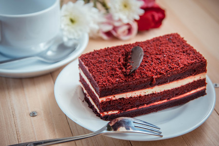 Red velvet cheese cake topping by dark  chocolate on white plate and fork put on wooden table. Cup of coffee and flower put near bakery cake. Stock Photo