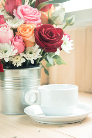Vase of bouquet Roses in aluminium bucket and white cup of coffee on wooden table, set of Beautiful flower Stock Photo