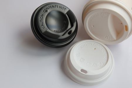 Black and white cover coffee cup, Caution: contents hot, disposable plastic cover protect the hot coffee on white background