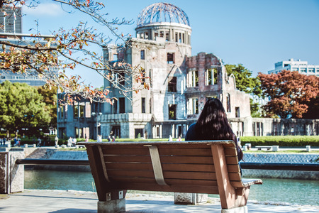 Girl sit on the bench, look at Atomic Dome from Hiroshima Peace Memorial park in the autumn season of Hiroshima, Japan.
