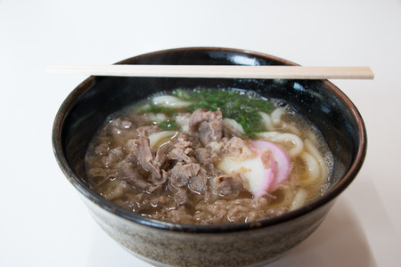 Big bowl of hot beef Udon, kuni Udon warm soup in winter season with fish ball and parsley traditional local Japanese food.