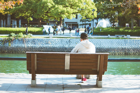 Man sit on the bench, look at Atomic Dome from Hiroshima Peace Memorial park in the autumn season of Hiroshima, Japan.