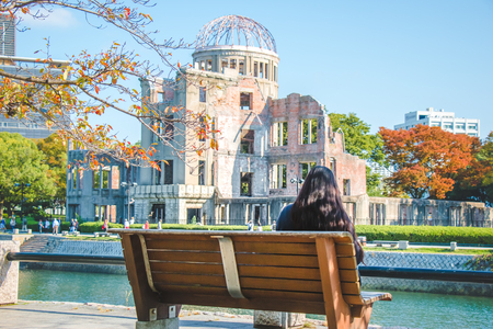 world war ii: Tree branch and red leaf in Autumn season, Girl sit on the bench, look at Atomic Dome from Hiroshima Peace Memorial park at Hiroshima, Japan.