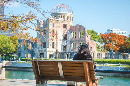 Tree branch and red leaf in Autumn season, Girl sit on the bench, look at Atomic Dome from Hiroshima Peace Memorial park at Hiroshima, Japan.