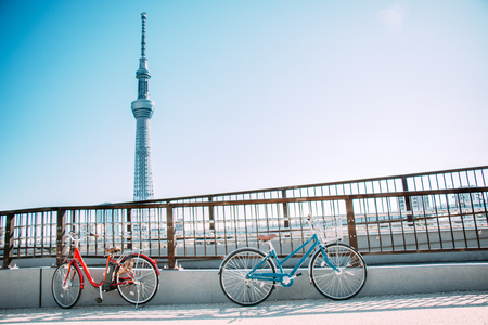Blue and Red Bicycle park at the railing of the bridge on the road along sumida river, see Tokyo sky tree at opposite site, Asakusa, Tokyo, Japan.