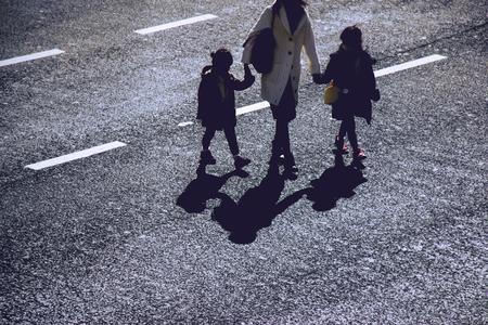 union familiar: La silueta de la madre celebra 2 manos de las muchachas a través de la calle en el empalme de Shibuya, Tokio, Japón. el punto de unión más famoso y popular de la gran corona en Tokio. Foto de archivo