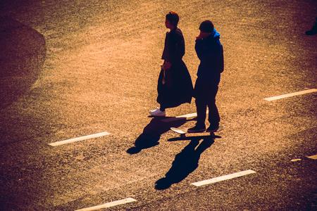 union familiar: Silueta de un par de cogidos de la mano a través de los peatones en Shibuya Junction, Tokio, Japón