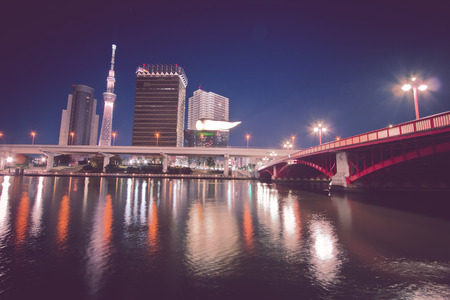 Night light view of Sumida river. Azumabashi Riverside, Red Bridge on the Sumida River, the opposite site can see Tokyo sky line, Asakusa, Tokyo, Japan. Editorial