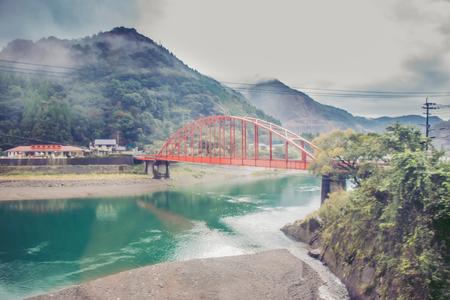 Big Mist in heavy rainy day, blur of Red iron bridge in big Cloud at Sakamotomachi storm is coming, Sakamoto, Yatsushiro, Kumamoto Prefecture.