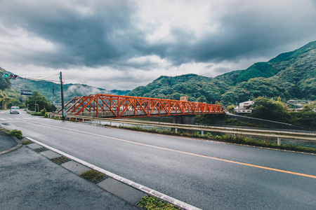 Red iron bridge at Sakamotomachi in heavy rainy day, storm and big cloud is coming, Sakamoto, Yatsushiro, Kumamoto Prefecture.
